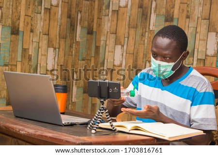 young african doctor wearing face mask isolated himself indoor carrying out research and making a video call #1703816761