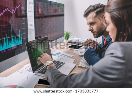 Side view of computer systems analysts using charts on computer monitors while working in office #1703833777