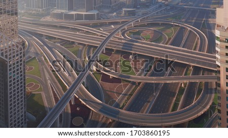 Aerial view of empty highway interchange in Dubai downtown after epidemic lockdown. Cityscapes with disappearing traffic on a bridge and streets. Roads and lanes crossroads without cars, Dubai, United #1703860195