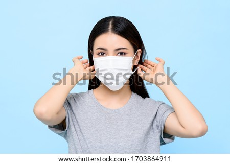 Asian woman wearing medical face mask isolated on light blue background #1703864911