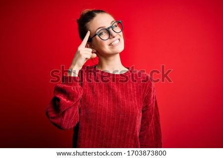 Young beautiful redhead woman wearing casual sweater over isolated red background Smiling pointing to head with one finger, great idea or thought, good memory