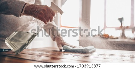 Close up of cleaning home wood table, sanitizing kitchen table surface with disinfectant antibacterial spray bottle, washing surfaces with towel and gloves. COVID-19 prevention sanitizing inside. Royalty-Free Stock Photo #1703913877