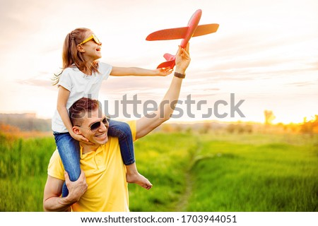 Cheerful man smiling and carrying excited girl on shoulders while playing with red aircraft together against cloudy sky on sunny summer day #1703944051