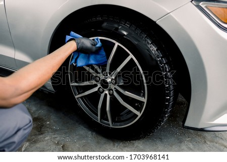 Car rims cleaning, car detailing wash concept. Cropped close up photo of male hand in black rubber glove with blue microfiber cloth washing car alloy wheel at car wash service #1703968141