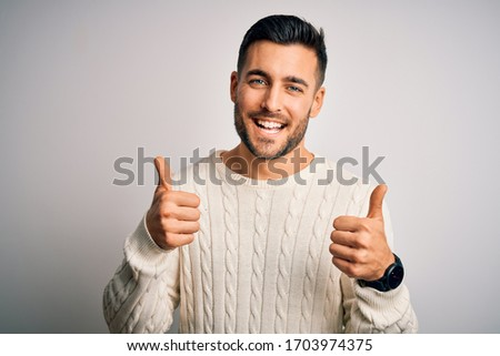 Young handsome man wearing casual sweater standing over isolated white background success sign doing positive gesture with hand, thumbs up smiling and happy. Cheerful expression and winner gesture. #1703974375