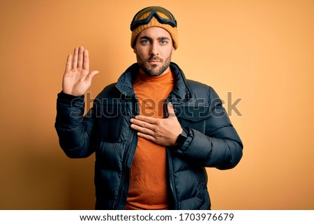 Young handsome skier man with beard wearing snow sportswear and ski goggles Swearing with hand on chest and open palm, making a loyalty promise oath #1703976679