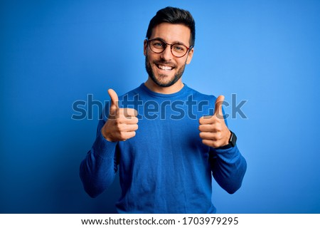 Young handsome man with beard wearing casual sweater and glasses over blue background success sign doing positive gesture with hand, thumbs up smiling and happy. Cheerful expression and winner  #1703979295