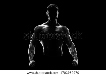 Silhouette of a strong fighter. Confident young fitness man with strong hands and clenched fists. Dramatic light. Royalty-Free Stock Photo #1703982970
