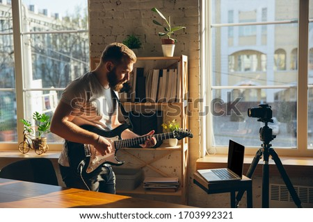 Caucasian musician playing guitar during online concert at home isolated and quarantined. Using camera, laptop, streaming, recording courses. Concept of art, support, music, hobby, education. Royalty-Free Stock Photo #1703992321