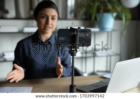 Modern smartphone gadget on tripod record young female speaker or coach making live broadcast on Internet, cellphone gadget shoot woman blogger or influencer talking for tutorial or webinar online #1703997142