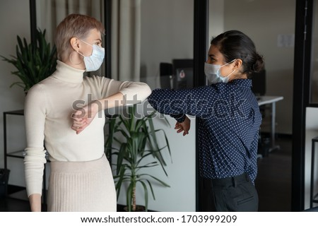 Smiling diverse female colleagues wearing protective face masks greeting bumping elbows at workplace, happy coworkers in medical facial covers protect from COVID-19 pandemics, healthcare concept Royalty-Free Stock Photo #1703999209