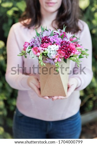 Girl holding beautiful pink flowers pot. Garden decor. Cover picture.  #1704000799