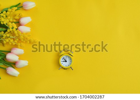 Spring flowers tulips and mimosa,yellow retro alarm clock on yellow background. picture for packages.Spring mood. Spring card for Mother's Day, Women's Day. copy space.Selective focus