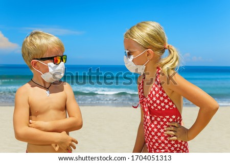 Two young funny children wearing sunglasses, protective mask on sea beach. Summer tours, cruises cancellation due to coronavirus COVID-19 world epidemic. Safe travel destinations for family vacation #1704051313