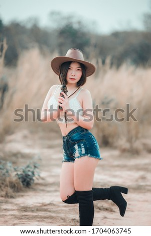 Portrait of asian woman wear cowgirl charactor at the field,Cowboy festival concept,Sexy lady pose for take a picture,Thailand people
