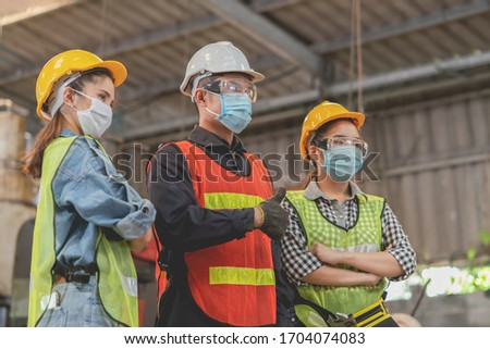 Group of Asian male and female engineers wearing hygienic mask protect with helmet safety in factory Industrial.Coronavirus Protective, safety concept #1704074083