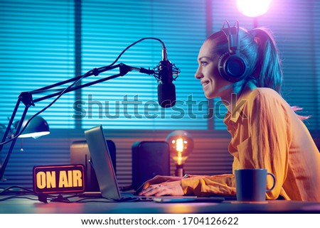 Young radio host working in the studio, she is smiling and broadcasting announcements Royalty-Free Stock Photo #1704126622