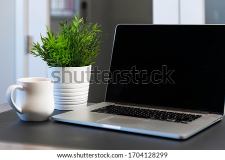 A laptop and coffee mug on a desk in a home office Royalty-Free Stock Photo #1704128299