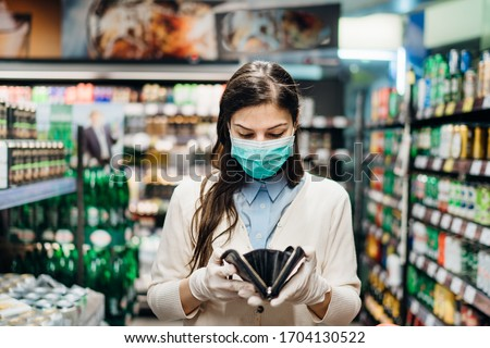 Worried woman with mask groceries shopping in supermarket looking at empty wallet.Not enough money to buy food.Covid-19 quarantine lockdown.Financial problems anxiety.Unemployed person in money crisis Royalty-Free Stock Photo #1704130522