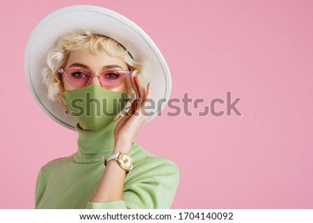 Woman wearing trendy fashion outfit during quarantine of coronavirus outbreak. Model dressed protective stylish handmade face mask, pink sunglasses, white hat, wrist watch, green mint color turtleneck #1704140092