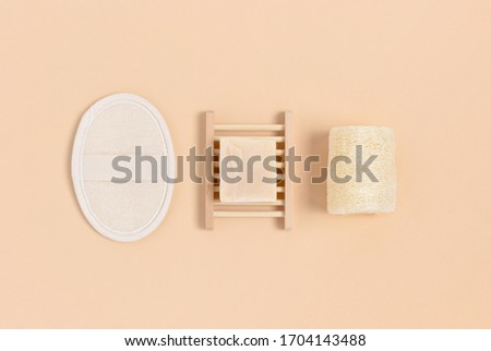 Handmade soap on a wooden dish, loofah sponges on a beige background. Eco lifestyle concept. Royalty-Free Stock Photo #1704143488
