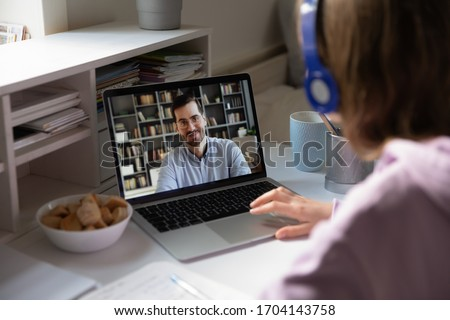 Student girl wearing headphones sitting at desk watching educational webinar, listen teacher during distant lesson via videoconference, view over woman shoulder laptop screen male tutor teach learner #1704143758