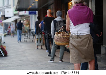Low angle and selected focus, European people queue and wait for shopping on sidewalk outside supermarket during quarantine for COVID-19 virus in Düsseldorf, Germany. #1704148564
