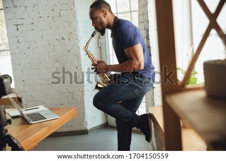 African-american musician playing saxophone during online concert at home isolated and quarantined. Using camera, laptop, streaming, recording courses. Concept of art, support, music, hobby, education Royalty-Free Stock Photo #1704150559
