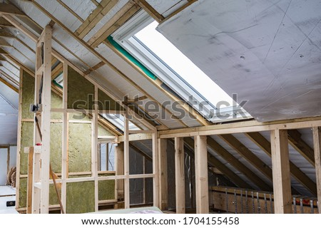 Loft conversion, unfinished project, silver insulation, roof windows, wood structure of the walls, selective focus Royalty-Free Stock Photo #1704155458