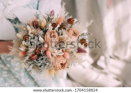 wedding bouquet of dried flowers in the hands of a florist Royalty-Free Stock Photo #1704158824