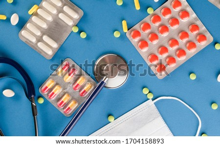 Phonendoscope, protective mask and pills on a blue background. #1704158893