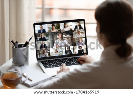 View over businesslady shoulder seated at workplace desk look at computer screen where collage of many diverse people involved at video conference negotiations activity, modern app tech usage concept Royalty-Free Stock Photo #1704165919