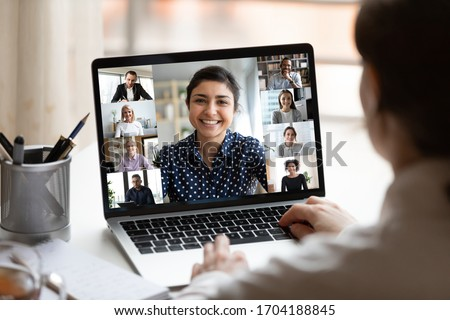 Woman sit at desk looking at computer screen where collage of diverse people webcam view. Indian ethnicity young woman lead video call distant chat, group of different mates using videoconference app Royalty-Free Stock Photo #1704188845