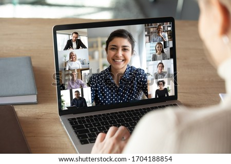 Laptop screen over woman shoulder view, indian businesswoman leading videoconference distant communication group videocall conversation. Diverse friends using modern tech enjoy virtual meeting concept #1704188854