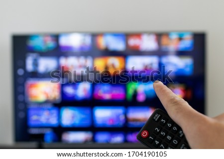 Remote controller and tv blurred in background. Video streaming service catalogue in grid blurred on smart TV.  #1704190105