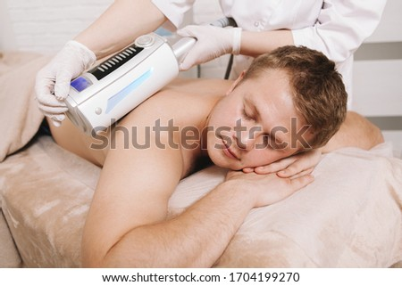 Relaxed man enjoying full body massage with endospheres massager by professional therapist #1704199270