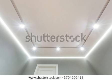 looking up on suspended ceiling with halogen spots lamps and drywall construction in empty room in apartment or house. Stretch ceiling white and complex shape. #1704202498