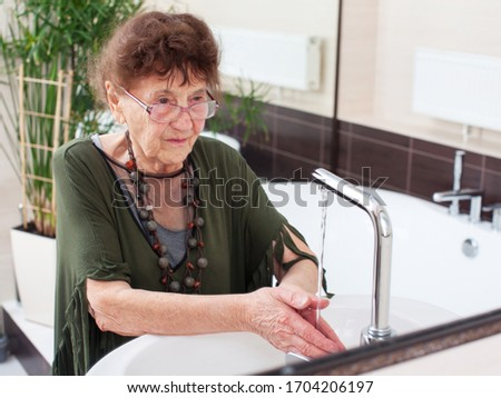 Elderly old woman washes her hands. Mature female at home #1704206197