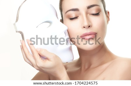 Beauty and skin care concept. Healthy skin model woman with led mask. Photon therapy light treatment skin rejuvenation led facial mask. led skin rejuvenation therapy. Isolated on white with copy space #1704224575