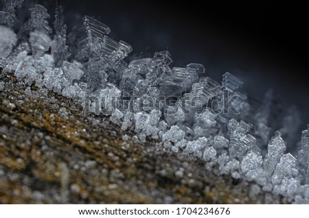 Frozen ice crystal dew frost picture of icy structure on wooden underground very detailed macro closeup of sharp sticking out frosty crystals