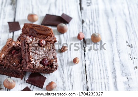 Fresh made homemade brownies made with from chocolate candy and hazelnuts over a a white rustic wooden table. Selective focus with blurred background.
