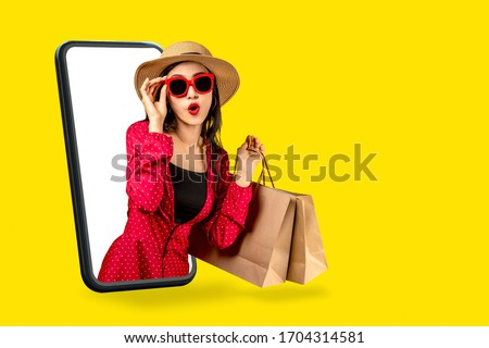 Young attractive asian female holding shopping bag feeling excited, happy and amaze on beauty or fashion online store discount promotion with concept tech on omnichannel e-commerce thru mobile screen. Royalty-Free Stock Photo #1704314581