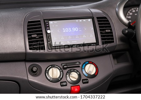 Novosibirsk/ Russia – April 02, 2020: Nissan March, close-up of the central control panel, monitor with music and radio , adjustment of the blower, air conditioner, player. modern car interior   #1704337222