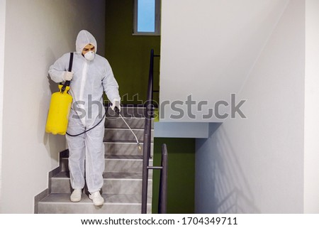 Sanitizing interior surfaces. Cleaning and Disinfection inside buildings, the coronavirus epidemic. Infection prevention and control of epidemic. Protective suit and mask. #1704349711