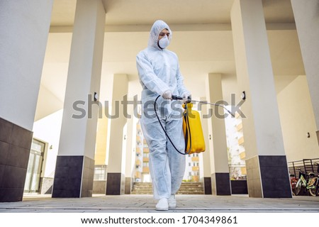 Cleaning and Disinfection outside around buildings, the coronavirus epidemic. Professional teams for disinfection efforts. Infection prevention and control of epidemic. Protective suit and mask. #1704349861