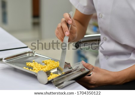 Pharmacist is counting pills on counting drugstore,Pills in pill counting tray,Orange tablets medicine on the drug count tray,Tablets medicine on the drug count tray, #1704350122