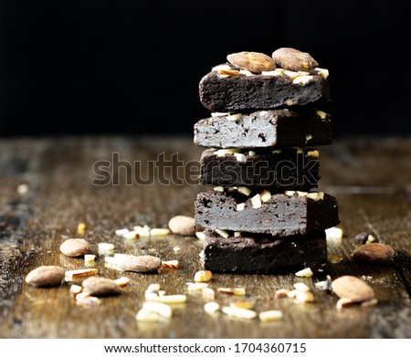 Black brownie almonds on wood table, close up picture. Food issue.