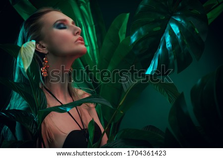 Beautiful sultry woman with wet hair stands among tropical plants. Beauty, fashion and cosmetics concept. Vacation in tropical countries. #1704361423