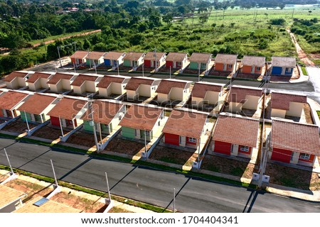 Aerial view of community houses in construction. Panoramic view of popular housing. Great landscape. Popular houses. Community housing. Construction landscape. Popular neightborhood houses.  Royalty-Free Stock Photo #1704404341