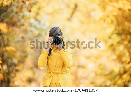 Aurlandsfjellet, Norway. Young Woman Tourist Photographer Taking Pictures Photos Of Autumn Yellow Forest Park. Lady Walking In Fall Park With Yellow Foliage.